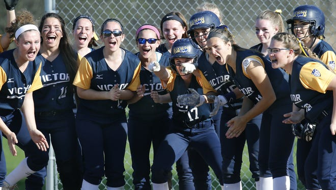 Victor teammates welcome Erin Wong at home plate during a game last spring at Rush-Henrietta.