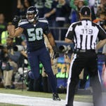 Seattle Seahawks outside linebacker K.J. Wright (50) celebrates after a play late in the fourth quarter of an NFL football game between the Seattle Seahawks and the Detroit Lions that was ruled a touchback after Lions wide receiver Calvin Johnson fumbled and the ball went across the end line of the end zone, Monday, Oct. 5, 2015, in Seattle as back judge Greg Wilson looks on at right. The Seahawks beat the Lions 13-10.