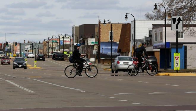 Two bikers cross Central Avenue near West 11th Street in Marshfield March 21, 2016.