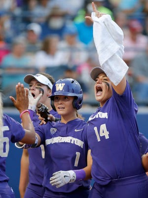 Washington's Ali Aguilar (1) celebrates with Taran Alvelo (14) after hitting a home run in the sixth inning against UCLA during the NCAA Women's College World Series in Oklahoma City on Saturday.