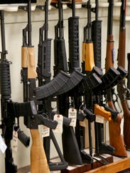 A rack displays a variety of rifles.