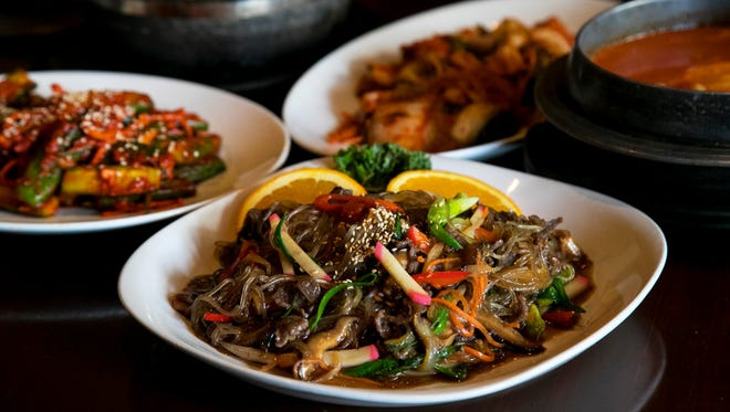 Some of the popular dishes at Origami include japchae, center, kimchi, soondubuchigae and bibimbap.
