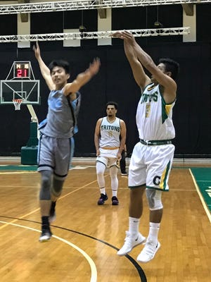 UOG's Ryan Nangauta hits a 3-pointer against GCC Monday night in a Guam Men's College Basketball League game at the UOG Calvo Field House.