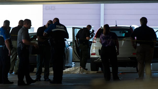 Law enforcement officers investigate the scene of a shooting death on the third floor of a parking garage on the corner of Main and Stone on Thursday, July 13, 2017.