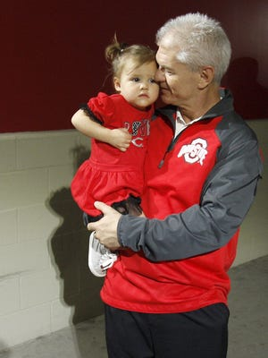 Ohio State football assistant coach and former Colerain head coach Kerry Coombs holds his 20-month-old granddaughter during the rain delay on Opening Night against the Pittsburgh Pirates, Wednesday, April 8, 2015, at Great American Ball Park in Cincinnati, Ohio.