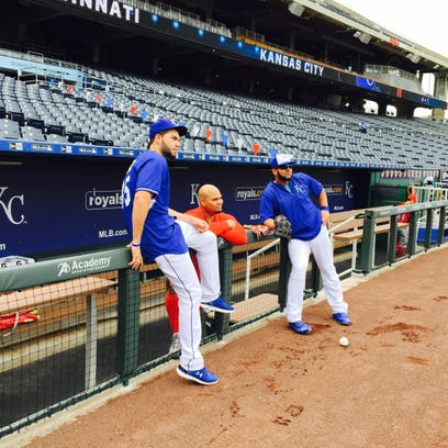 The Reds' Brayan Pena visits with former Kansas City Royals teammates Eric Hosmer (left) and Kendrys Morales in their dugout.