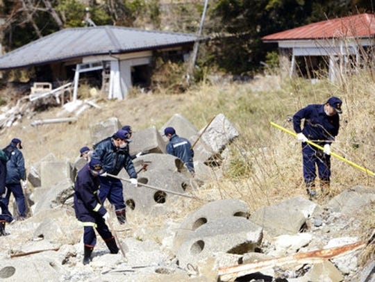 Police officers conduct search operation in Tomioka,