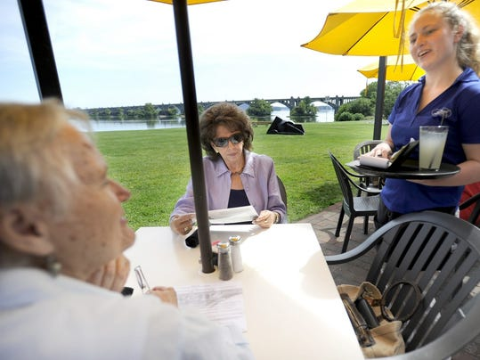 Server Sara Newcomer, right, takes a lunch order from Maryann Demagall, left, and Saundra Gilbert, center, of Mechanicsburg at John Wright Restaurant in Wrightsville.