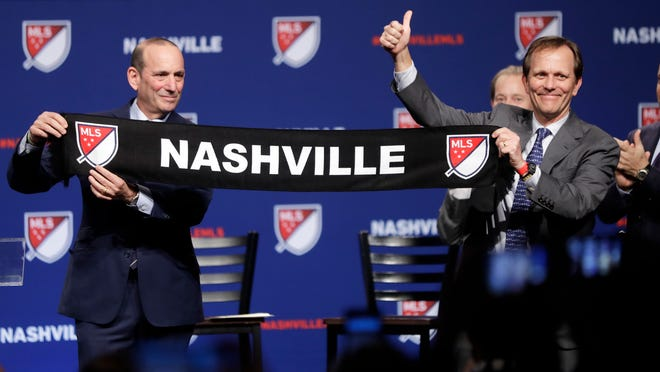 Major League Soccer commissioner Don Garber, left, presents a scarf to John Ingram, chairman of Ingram Industries Inc., as Garber announces that Nashville, Tenn. has been awarded a Major League Soccer franchise Wednesday, Dec. 20, 2017, in Nashville, Tenn. Ingram is the head of the group seeking to bring the team to Nashville. (AP Photo/Mark Humphrey)
