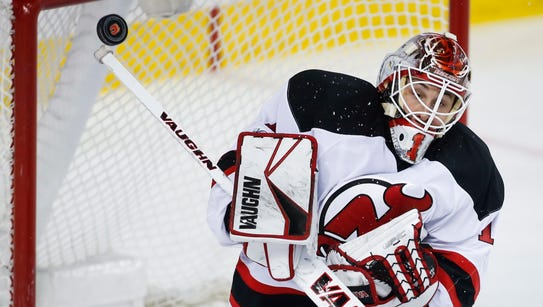 Devils goalie Keith Kinkaid deflects a shot by the