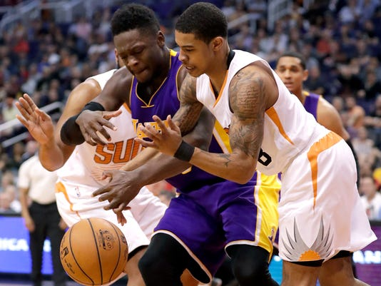 Phoenix Suns guard Tyler Ulis, right, and Los Angeles Lakers forward Julius Randle compete for the ball during the second half of an NBA basketball game, Thursday, March 9, 2017, in Phoenix. (AP Photo/Matt York)
