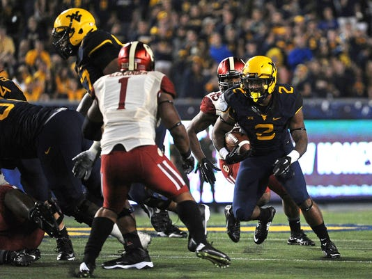 West Virginia running back Dreamius Smith (2) prepares to make a cut past Oklahoma defender Dominique Alexander in the fourth quarter of an NCAA college football game in Morgantown, W.Va., Saturday, Sept. 20, 2014. Oklahoma won 45-33. (AP Photo/Tyler Evert)
