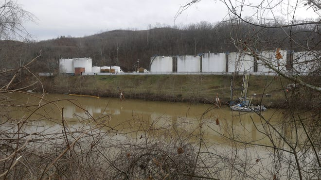 Workers inspect an area outside a retaining wall around storage tanks where a chemical leaked into the Elk River at Freedom Industries storage facility  in Charleston, W. Va., Monday, Jan. 13, 2014.