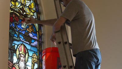A technician with the Emil Frei Studio works on a window at the Basilica of St. Michael the Archangel in January.