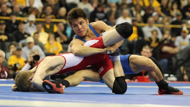 Henry Cejudo (blue) takes down Nick Simmons (red) during the 55kg freestyle match on April 22, 2014, at Carver Hawkeye Arena in Iowa City,  Iowa.