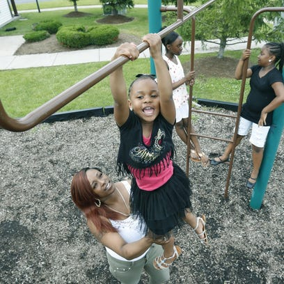 Tyesha Boone holds her daughter Tahani Smith, 4, as