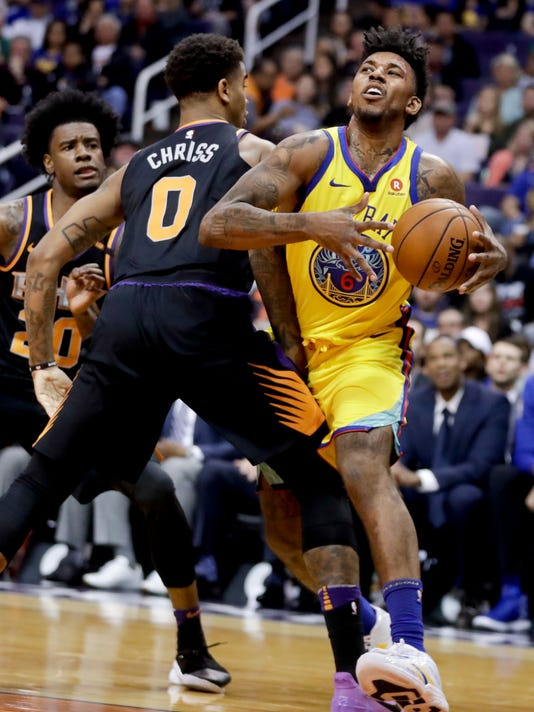 Golden State Warriors guard Nick Young, right, is fouled by Phoenix Suns forward Marquese Chriss during the first half of an NBA basketball game in Phoenix, Saturday, March 17, 2018. (AP Photo/Chris Carlson)