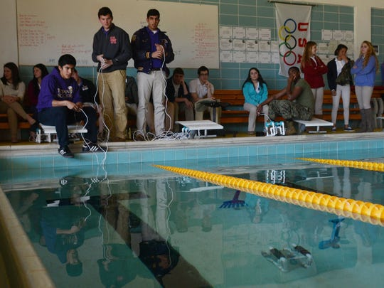 Alexandria Senior High students Jonathan Turrubiartes (far left), Zachary Price and Ahmad Salam are in Julia James' physics class and have built underwater robots. Turrubiartes and Price operate their robot with a remote control to have it complete an underwater obstacle course in the ASH swimming pool Wedneday, Jan. 28, 2015. A grant from SeaPerch covered equipment, lesson plans, guidelines and tools to create them, said James. SeaPerch is an innovative underwater robotics program that equips schools with resources to build an underwater ROV in an in-school setting, according to its website.