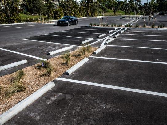 A car drives through the parking lot at Clam Pass Park