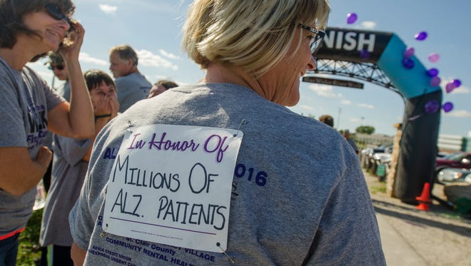 Bridget Whitican, of Emmett, wears a race bib in honor of all Alzheimer's patients Sunday, Sept. 25, during the Alzheimer's Walk along the River Walk in Port Huron.