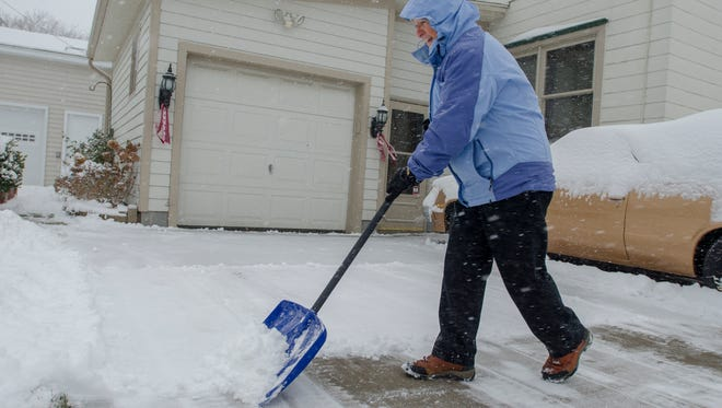 Donna Kelly gets to work shoveling her drive way Sunday, Dec. 11, in Port Huron.
