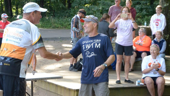 Dr. Peter Jeffrey Colquhoun is congratulated after placing second in his age group at Saturday's Shermanator Triathlon in Augusta.