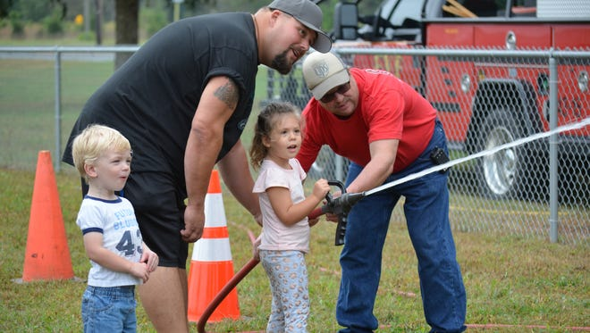 Marianna Gemenden, 3, of Franklinville works the fire hose with assistance from her father, Tex Gemenden, and Frankilnville firefighter Don Cross as Kasey Brendt, 3, of Harrisburg, Va., watches during the Family Fun Day & Health Fair that was hosted by Franklinville Volunteer Fire Co. No. 1 on Saturday, Oct. 14 at the Caroline L. Reutter School.