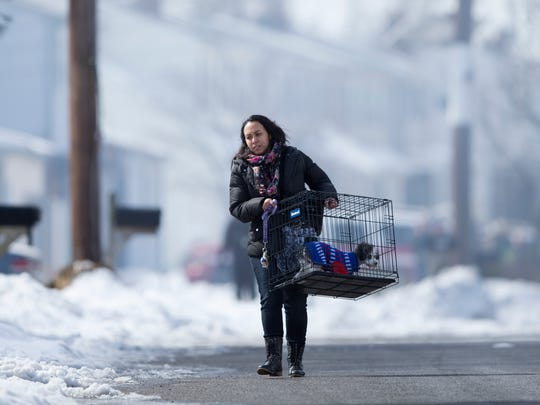 A woman evacuates with her dog after a tanker truck carrying nearly 9,000 gallons of fuel caught fire nearby, spewing thick, black smoke into the sky, Monday, Feb. 23, 2015, in Pennsauken, N.J. Nearby homes were being evacuated as a precaution, and traffic was being diverted. (AP Photo/Matt Rourke)