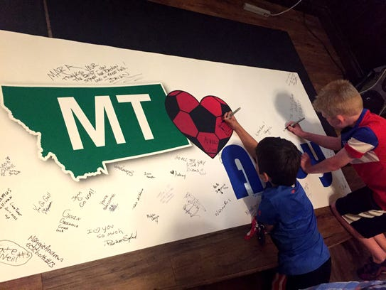Kids sign a banner at The Celtic Cowboy for Abby Wambach