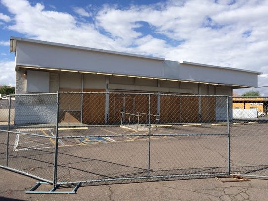 There are two empty, fenced-off convenience stores