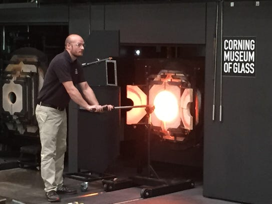 Glass artisan puts creation in furnace at Hot Glass