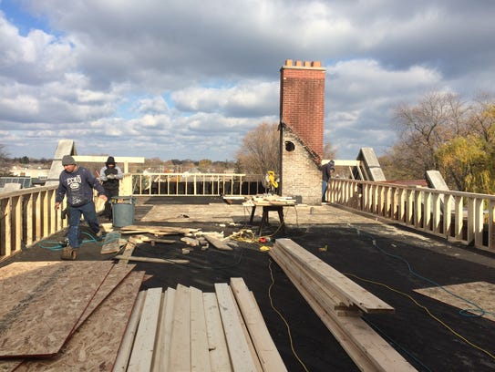 A construction crew repairs and reinforces the roof