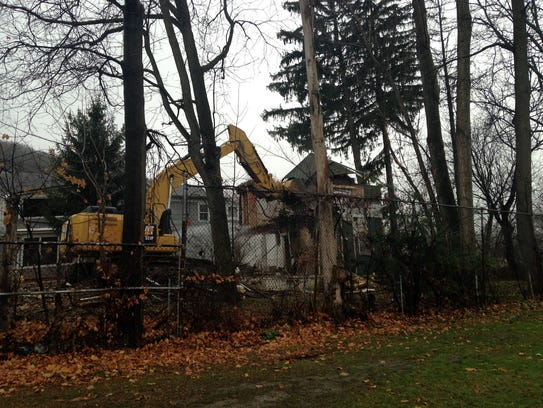 An excavator works at demolishing a house at 10 Alfred