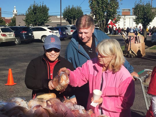 Volunteers Cathy Phillips, left, and Gary Evans, center,