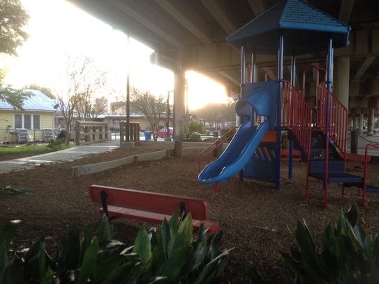 Playground equipment and park benches are part of a