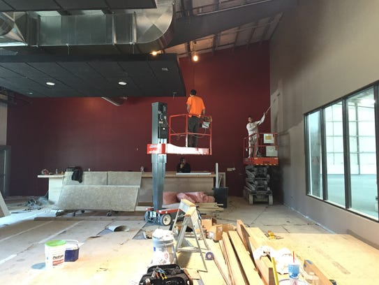 Workers paint the tasting room at the new Three Heads