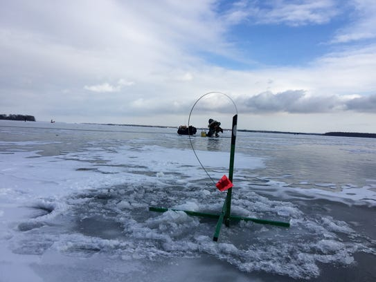 An ice-fishing tipup rig waits for nibbles on its baited
