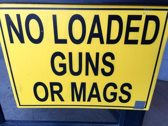 A sign outside the expo warns visitors that no loaded