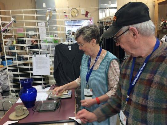 Veteran worker Jackie Choate (left) works on processing