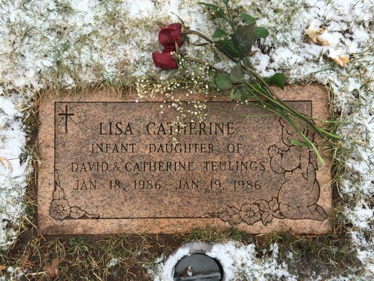 Dave and Cathy Teulings put red roses on their daughter
