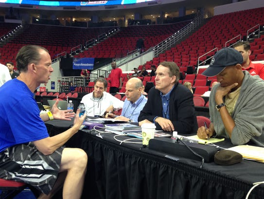 FGCU coach Joe Dooley, left, talks to the TNT broadcast crew, including announcers Reggie Miller, right, and Kevin Harlan, seated, far left, after NCAA tournament practice Wednesday, March 16, 2016, at PNC Arena in Raleigh, North Carolina.