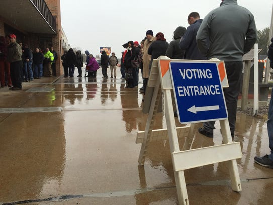 Voters wait in line Tuesday in the village of Plover.