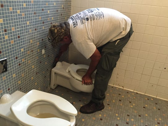 Jimbo Riner removes a toilet in a restroom at the Fort