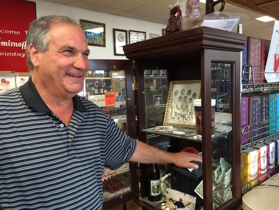 Colonial Liquors owner Bobby Bubis rubs the urn in