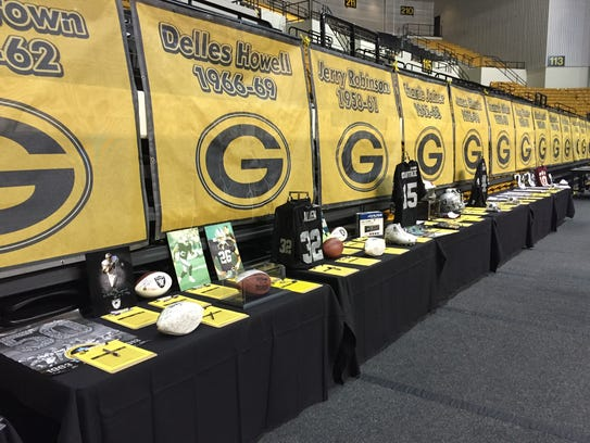 Sports memorabilia for a silent auction lines a wall