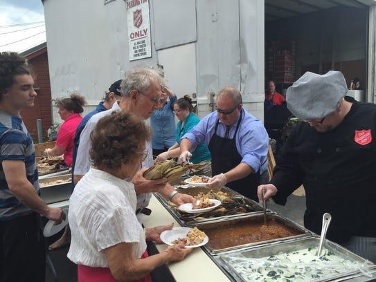 Mayor Robert Mielke (center) serves food to those waiting