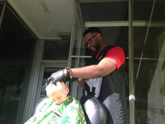 Devante Ellis cuts Landon Gordon's hair outside Diversified