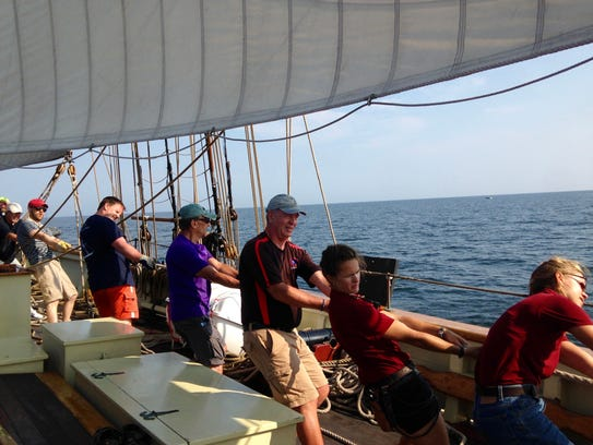 Passengers help man the ship aboard the Pride of Baltimore