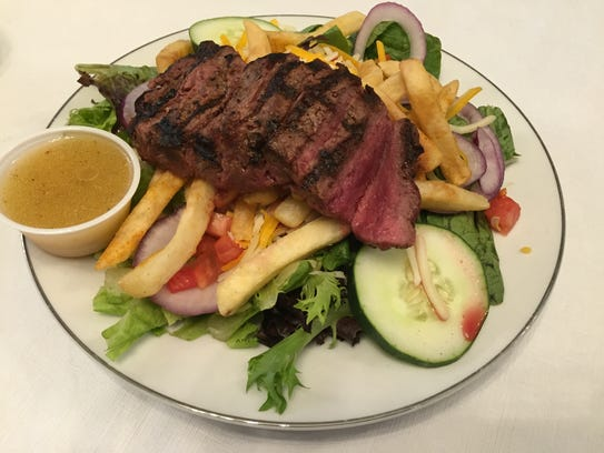 Pittsburgh steak salad is topped with fries at the