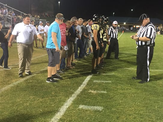 Former Rebel football players  accompany their coach,